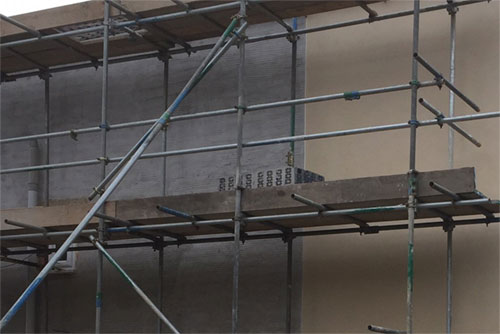 scaffolding on brick house colour rendering preparation with scratch coat render applied